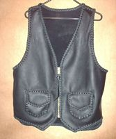 biker leather vest with a zipper, pockets, a back yoke, and a draft flap on the back
