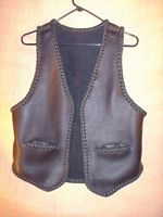 "This black braided moccasin leather vest has slit hip pockets and a 3"" draft flap at the back/bottom of it."