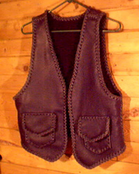 This black motorcycle leather vest was custom made in the USA with moccasin cowhide. It has two patch hip pockets with flaps and two more similar pockets on the inside using the same braiding to attach them. These inside pockets do not have flaps.