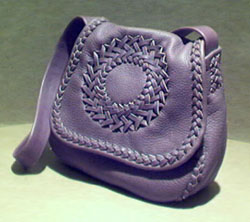 A bag using what is called the 'S' applique braid. It has a circle applique on the flap, a full width inside back pocket, and a flat wide/strong shoulder strap.