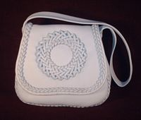 This is the front view of this Pearl colored, braided leather purse on a dark colored background.