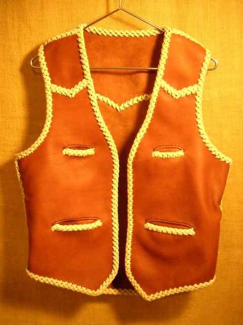 "This moccasin cowhide leather vest was made in the USA. It features both front and back yokes that are all pointed. It has two slit breast pockets (credit card size) and two slit hip pockets. It also has the curved 3"" draft flap extension at the back/bottom."