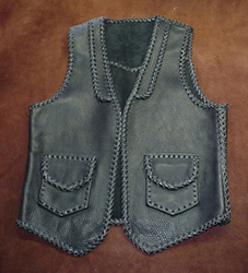 This leather vest has all of it's sams and edges braided. It also has braided lapels on the front, a pointed yoke on the back, and two patch hip pockets with flaps. It also has matching hip pockets on the inside of the front (without flaps). By clicking on the link, you will see more closer up pictures of it.