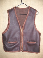 This two tone Brown leather vest is completely hand braided using moccasin cowhise tanned in the USA. It featurs a large brass (YKK #10) zipper and two slit hip pockets. At the buyers request, this was is squared off completely across the bottom (front and back panels).