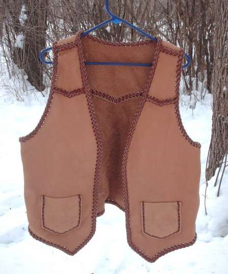 The buffalo (American bison) leather this vest was built with was provided by the buyer - the lacing for it is my moccasin cowhide leather. It has pointed yokes on the front and back, two patch hip pockets (without flaps) that also have matching inside pockets = four pockets in total.