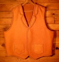 This custom and handmade leather vest was made in the USA with moccasin cowhide that was tanned in the USA. All of it's features were decided by the buyer. Those features are front split yokes, a back pointed yoke, two patch hip pockets, and conchoes that I fashioned to hang straps from.