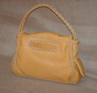 The back side of this purse has the braided oval slot to access the large back pocket that it has.