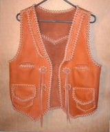 This Western style leather vest has front lapls, a back pointed yoke, two slit breast pockets, two patch hip pockets with flaps (with matching inside pockets without flaps), a back/bottom draft flap, and concoes that I fashioned for straps to hang from. Clicking on the link will bring you to more close up pictures of these features.
