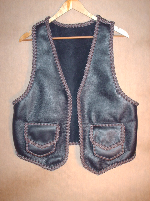 This two tone (black and brown) moccasin cowhide leather vest has patch hip pockets with flaps - these include inside pockets (without flaps). It's large arm hole built for wearing over a jacket.