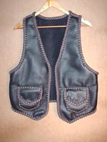 a two tone black and brown leather vest built to accomodate it being worn over a jacket