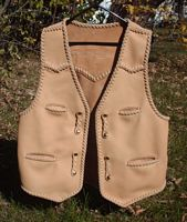 This custom leather vest was hand made in the USA for the buyer. Made of moccasin cowhide, it featurs frony pointed yokes, a back pointed yoke, two slit breast pockets (credit card size), two slit hip pockts, and with four sets of 'trick braid' straps for snap closures. It also has (what I call) a back/bottom draft flap.