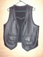 This custom black leather vest was made with moccasin cowhide leather. It's features include lapels on the front, a back pointed yoke, and two patch hip pockets with flaps. On the page that this picture is linked to is a picture of the back of it.