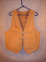 This moccasin cowhide leather vest was hand made in the USA using leather that was tanned in the USA. It features lapels, a pointed back yoke, two front slit breast pockets (credit card size), two patch hip pockets (without flaps), and two set of 'trick braid' snap closures. Clicking it's link brings you to a page with some close up of these features.