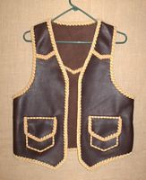 Like all of my work, this custom and handmade leather vest was built to the customers specifications. It has pointed yokes (front and back), and patch hip pockets with flaps. The two colors are both brown tones ...with lots of contrast.