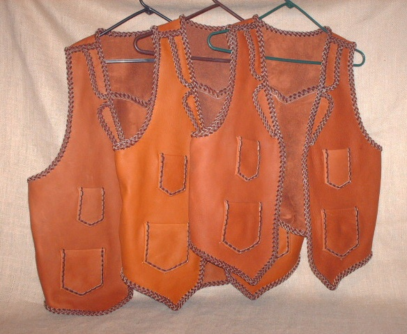 These three two toned vests were all bought by the same guy for his bartender employees. They all have split lapels, pointed yokes on the back, as well as, the four pockets done with a simple braid. All of my work is made in the USA using leather tanned in the USA