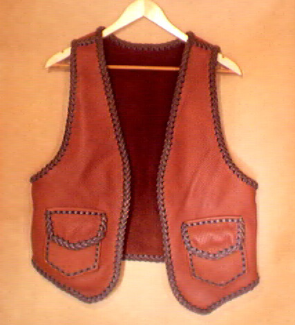 This two tone brown handmade leather vest was custom made in the USA with moccasin cowhide leather that is tanned in the USA. It has patch hip pockets with flaps and, on the inside, it has matching pockets without flaps.