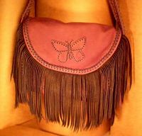 The woman that purchased this bag wanted it very elaborate. It has fringe hanging from the flap and from the two side pockets. The long flat strap employs three lengths of braiding - one down the center and edge braiding along each side of it.