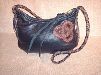 A Black and Mahogany bag with a Mahogany tri-loop applique on one side of it. The same two colors are used for the strap which has short tassels.