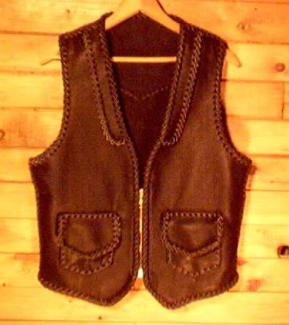 This black leather vest was hand braided and made in the USA using moccasin cowhide leather that is tanned in the USA. It has front lapels, a back pointed yoke, patch hip pockets with flapd (with matching inside pockets - No flaps. It also has a large brass, (YKK #10) zipper. Each vest that I construct is built to th details that the buyer has requested.