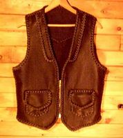 a bikers vest with a zipper closure, pockets with flaps, and a yoke on the back leather vests custom made and braided