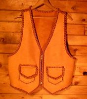 a two tone vest that has pockets with flaps and large arm holes for wearing over a jacket  leather vests custom made and braided