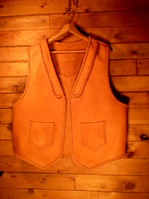 This moccasin cowhide leather vest was custom built for the buyer. It has lapels on the front, a pointed yoke on the back, and two patch hip pockets that also have matching pockets on the inside.