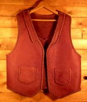 This custom built vest was made in the USA using moccasin cowhide leather tanned in the USA. It has lapels in front and a pointed yoke on the back. It's patch hip pockets are attached with a simple braid and these pockets also have matched pockets on the inside (four pockets in all). Click the linked picture for more about it.