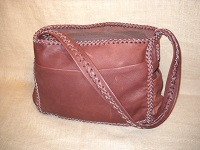 This large cowhide leather bag is similar to the other bags in this section, but, it has an open top - no flap. It has pockets on all four sides and a strap that is braided down the length of it.