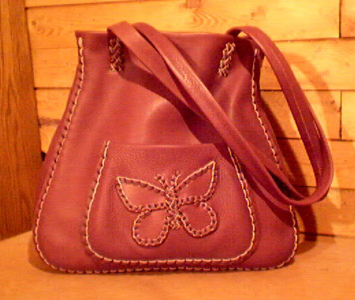 large leather tote bag with a braided leather butterfly on the pocket