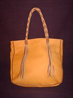 This is the back view of the tote that also shows the braided straps and their long tassels.