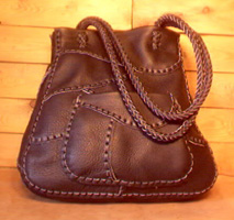 This large Black tote was built with small pieces of leather braided together. It has the front pocket you see in the picture and another full width pocket on the inside/back. It also has long 8 strand braided straps.