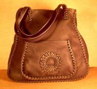 a tote bag made using braided leather with a circle applique on the front pocket