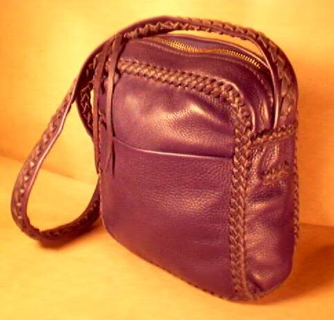 a large zippered bag made with a large brass zippered closure and a long braided leather shoulder strap