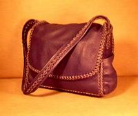 "This dark Brown moccasin cowhide leather man bag is completely constructed with leather lacing/braiding. It is 100% leather - it has no hardware, no lining, nor thread. It has elaborately braided seams, as well as, around the flap, and down the length of its wide strap. The dimensions of it are about 14.5"" wide by 12"" high by 4"".   It has four pockets - one full width on the front under the flap that is 9"" high. There is another full width pocket on the inside back that is 9'5"" high. It also has pockets on each sides that are about 4"" wide by 6"" high."
