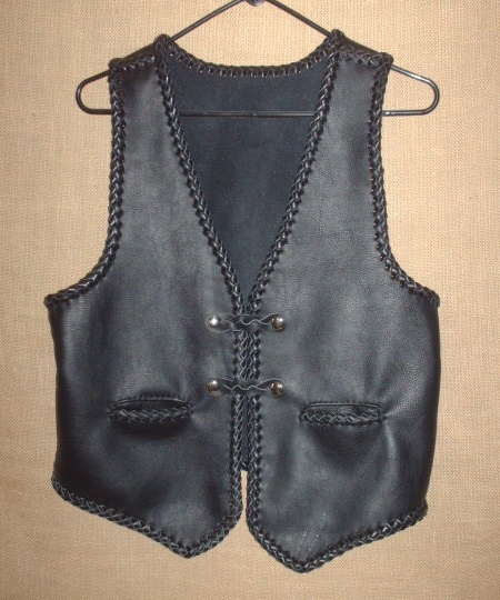 This moccasin cowhide leather vest has all of it's edges and seams braided. It has two slit hip pockets (with braiding) and two sets of 'trick braided' snap closures. It's all hand braided and made in the USA using leather that was tanned in the USA