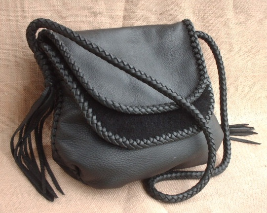 "This large black leather shoulder bag is completely built with various leather braids using 1/4"" wide laces. The double flaps have an edge braid, and the seams are done with an applique braid, the strap is an 8 strand round braid that has 8 long tassels that hang from each end of it."