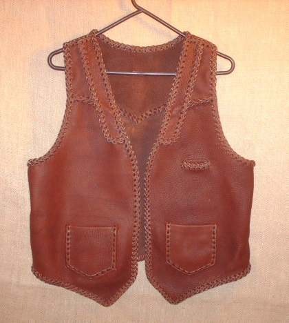 This brown moccasin cowhide leather vest has both lapels and slanted yokes on the front of it - that's what the buyer wanted. It also has a pointed back yoke, a single slit breast pocket (credit dard size), and two patch hip pockets (with matching inside pockets).
