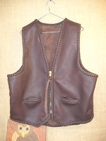 This Brown leather vest, whose seams and edges are completely braided. It has two slit hip pockets, a brass (YKK #10) zipper closure, and what I call a draft flap at the bottom of the back.