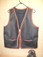 This braided (seams & edges) moccasin cowhide vest has no yoke/s, lapels. It does have two slit hip pockets and a large brass (YKK #10) zipper.