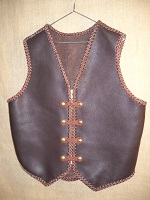This two tone leather vest was built with moccasin cowhide. It has 4 sets of 'trick braided' snaps and a zipper for closure. It has no pockets. It does have the back/bottom draft flap that many folks like.
