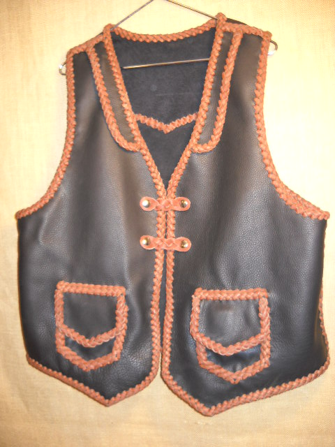 This two tone vest is built with moccasin cowhide leather including for the braided lacing. It has front lapels, a back pointed yoke, patch hip pockets with flaps and two sets of snap closures braided with what is called a 'trick braid'.