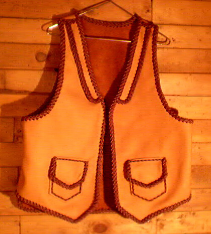 This two tone moccasin cowhide vest has front lapels, and two patch hip pockets with flaps. Patch pockets most always come with matching inside pockets using the same braiwork to attach - the inside pockets have no flaps.