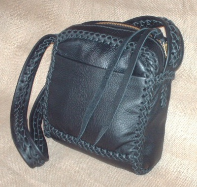 "This Black messenger purse is about 8"" wide by 8.5"" high by 3"". It has two full width pockets - one on the outside front and another on the inside back. It has no side pockets. Besides all the seams be braided together, it's 1-1/2"" wide strap has braiding down the center length of it."