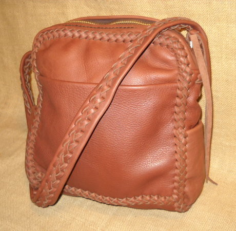"These messenger leather purses are built using a braided construction method with strong, supple, long lasting 4 oz. moccasin cowhide leather. Handmade, no electricity is used to build them. They all have large brass zippers (YKK #10) that are attached with hand sewn 5 ply nylon thread. This particular bag is made with Rust colored leather. The dimensions of it are about 10"" wide by 11"" high by 4"". It has a full width pocket on the front and another full width pocket on the inside/back. It also has pockets on each side whose 4"" width make them quite usable."