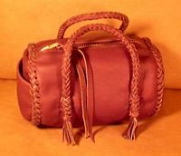 "This small Mahogany colored barrel bag has a large brass zipper and is about 7"" long with a 5"" diameter. It has two 8 strand round braided handles with short tassels hanging from the ends of them."