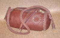 "This braided Mahogany bag has a large brass zipper and is about 9"" long by a 5"" diameter. It has an 8 strand round braided shoulder strap with short tassels on the ends of it. There is a braided circle applique on the side of it."