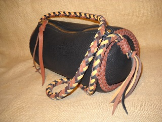 "Here is one of the many bags on this page that I call my 'barrel bags' - it is about 12"" long and has a 6"" diameter. The bag has a large brass zipper across the top of it. It's dark Brown bag with a Rust colored seam braided on each end of it. The 8 strand round braided strap is of four colors."