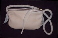 small leather shoulder bag with a long braided strap