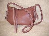 This Mahogany colored leather bag has a large #10 YKK zipper that has leather attached to the slide. It has braided seams and an 8 strand braided strap that has short tassels hanging from it.