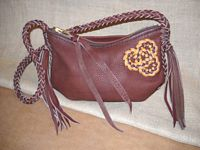 These two pictures are of a small Mahogany colored leather shoulder bag with seams that are elaborately braided. It has an 8 strand braided strap with 8 long tassels that hang from each end of it. It has a two-toned Celtic tri-loop knot braided on the side of it.